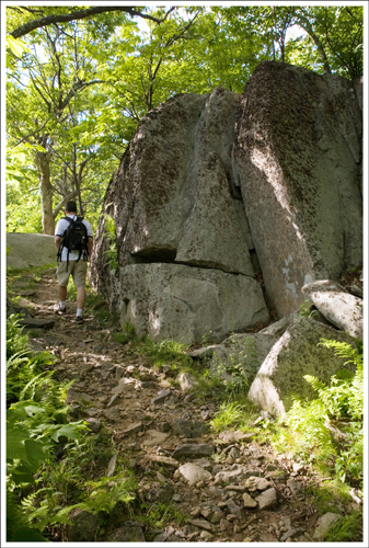 The trail is rocky and passes many large boulders.
