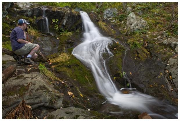 Adam sits alongside Lands Run Falls.