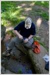 Adam Filtering Water from Gravel Spring